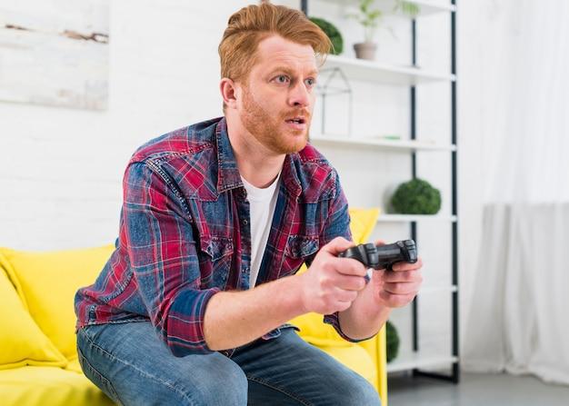 Homem novo sério que joga o jogo com controlador video em casa Foto gratuita