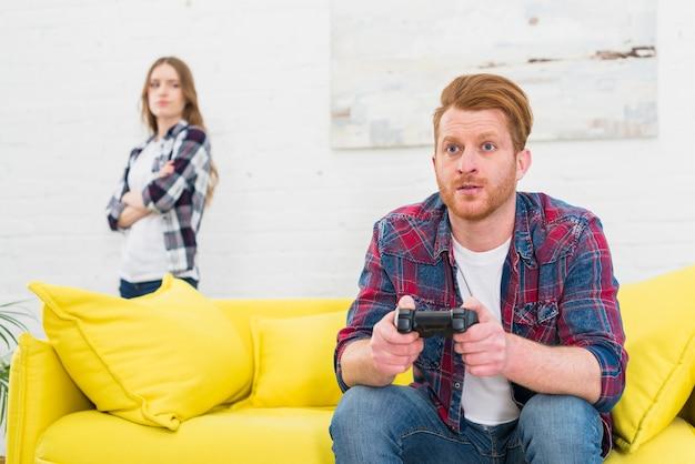 Homem novo sério que joga o jogo com o controlador video com sua amiga que está no fundo Foto gratuita