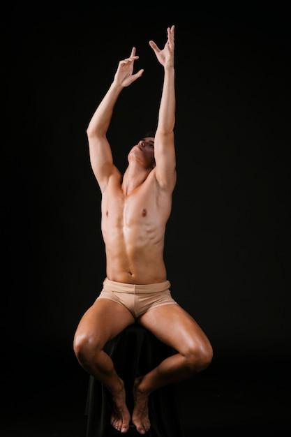 Homem nu, estendendo-se com as duas mãos Foto gratuita
