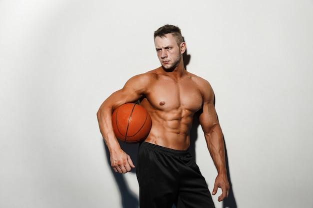 Homem nu muito musculoso segurando uma bola de basquete no estúdio Foto Premium
