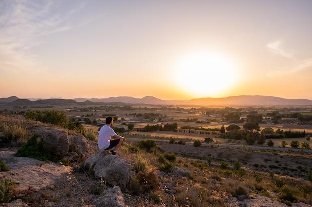 Homem, observar, a, pôr do sol, em, um, montanha Foto Premium