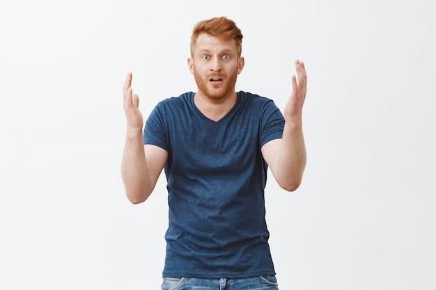 Homem olhando para o que restou de seu carro, sentindo-se chocado, parado sobre uma parede cinza em estupor. retrato de homem ruivo europeu surpreso, desapontado e chateado, gesticulando com as palmas das mãos e deixando cair o queixo Foto gratuita