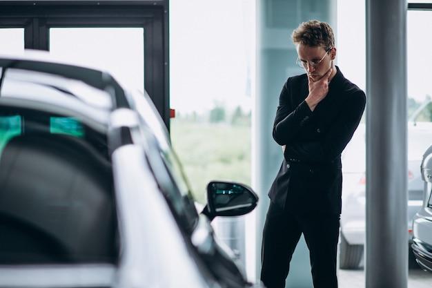 Homem olhando para um carro e pensando em uma compra Foto gratuita