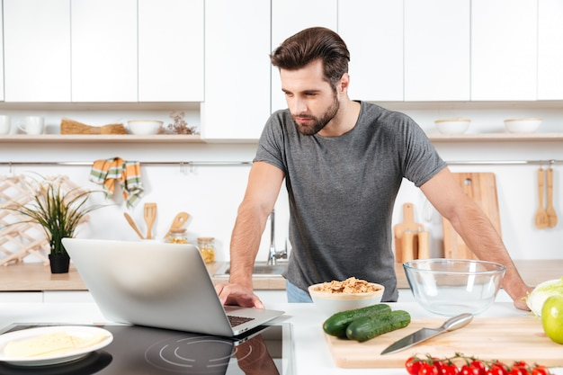 Homem olhando receita no laptop na cozinha em casa Foto gratuita
