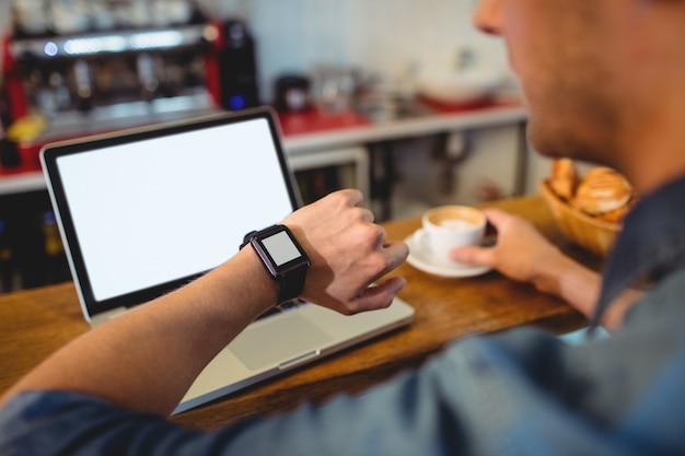 Homem olhando relógio inteligente no café Foto Premium