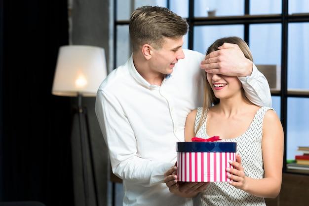 Homem, olhos cobrem, de, mulher, com, grande, caixa presente Foto gratuita