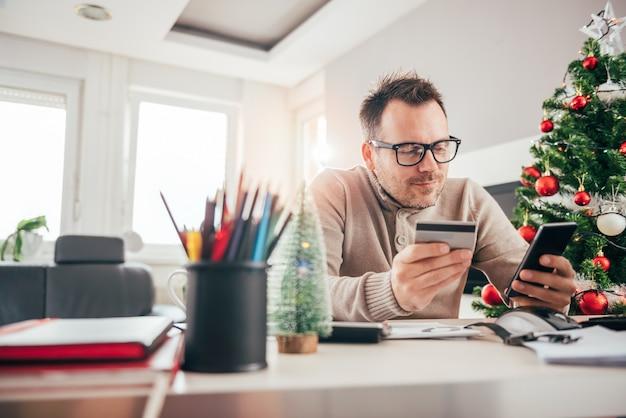 Homem pagando com cartão de crédito no telefone inteligente Foto Premium