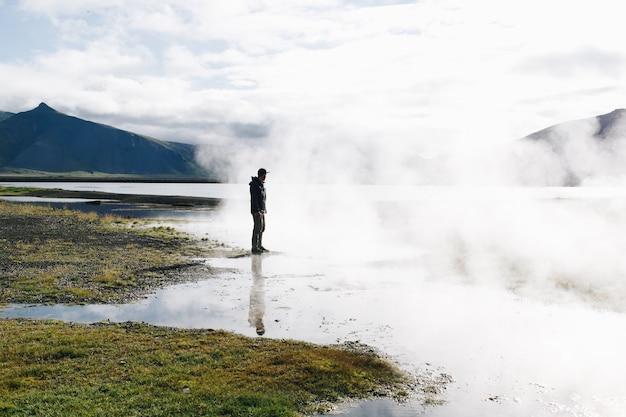 Homem parado sobre o lago gêiser na islândia Foto gratuita
