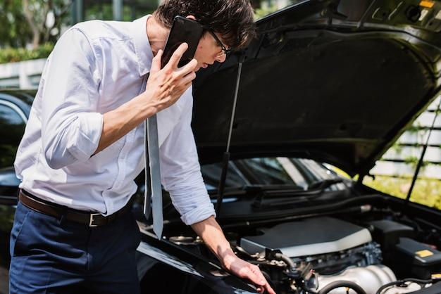 Homem pedindo ajuda para consertar seu carro Foto gratuita