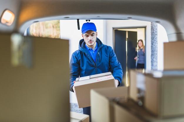 Homem pegando caixa para carro Foto Premium