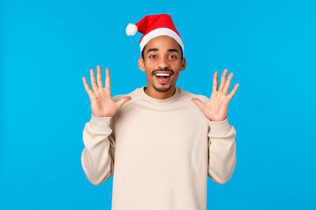 Homem pegando presentes no chapéu de papai noel. alegre jovem afro-americano pegar algo, levantando as mãos e esperando a captura, sorrindo com alegria, comemorar férias de inverno, parede azul Foto Premium