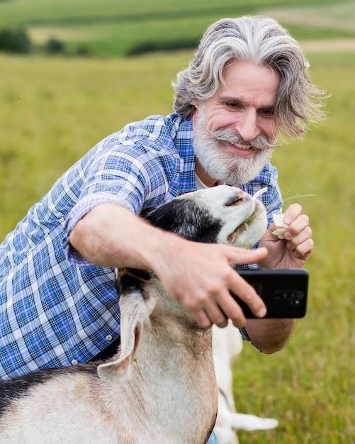 Homem pegando slefie com cabra Foto gratuita