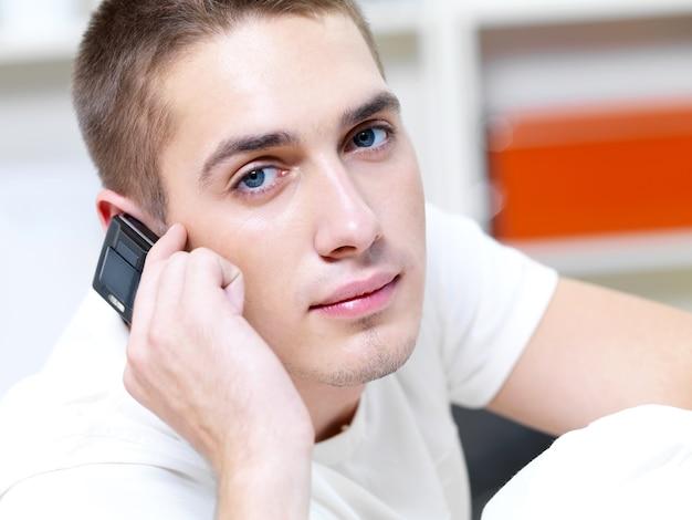 Homem pensativo chamando no telefone em branco Foto gratuita