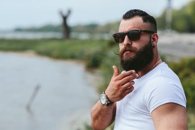 Homem pensativo com a barba ao ar livre Foto gratuita