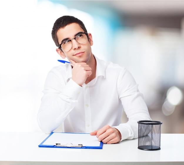 Homem pensativo com uma mesa de caneta esferográfica e verificação Foto gratuita
