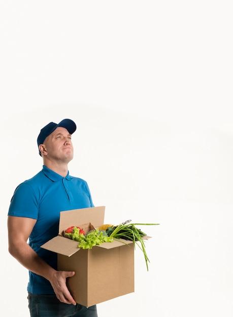Homem pensativo entrega posando com caixa de supermercado Foto gratuita