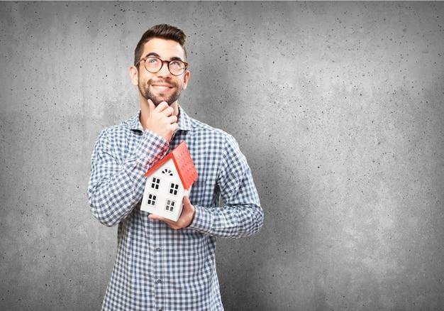 Homem pensativo que prende uma casa em miniatura Foto gratuita