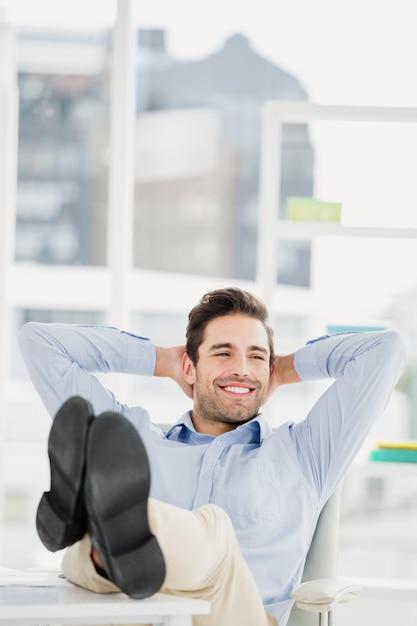 Homem pensativo, sentado com os pés na mesa Foto Premium