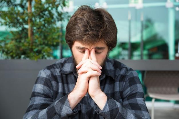 Homem pensativo tocando a ponte do nariz e pensando no café de rua Foto gratuita