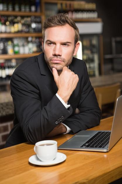 Homem pensativo usando laptop e tomando um café Foto Premium