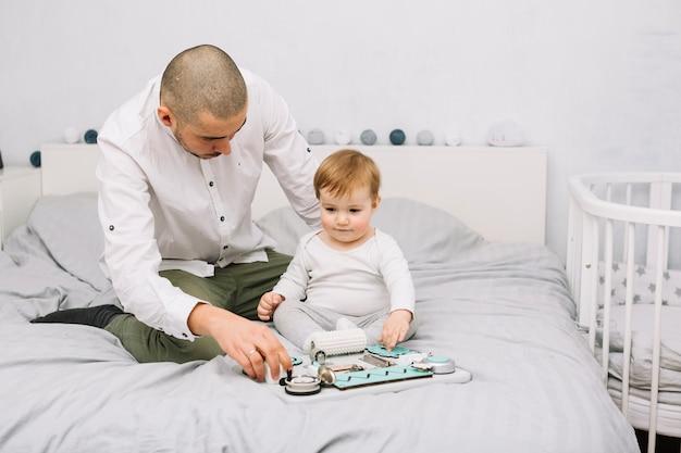 Homem, pequeno, bebê jogando, com, brinquedo, cama Foto gratuita