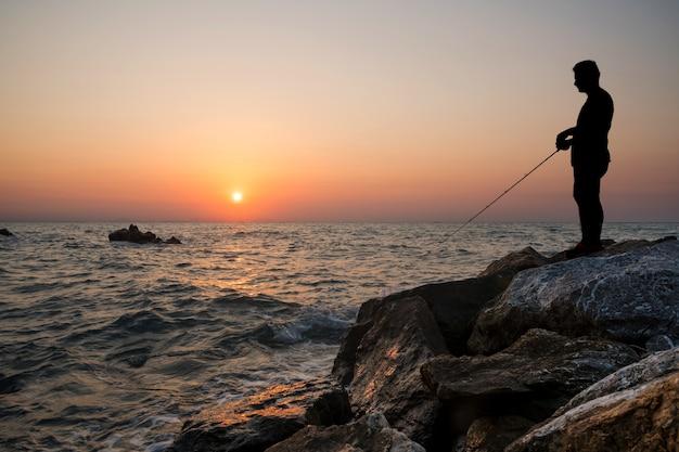 Homem pesca, pôr do sol Foto Premium