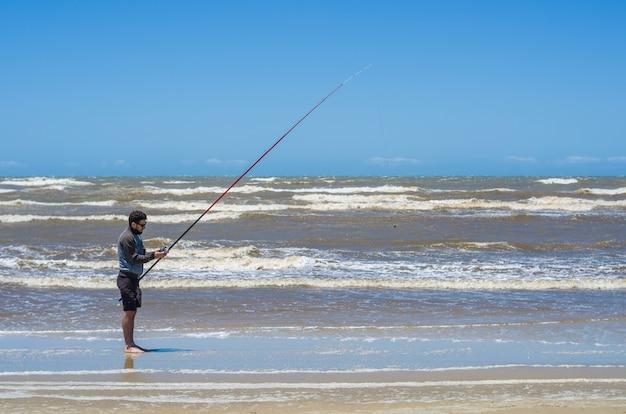 Homem pescando na praia, pesca esportiva Foto Premium