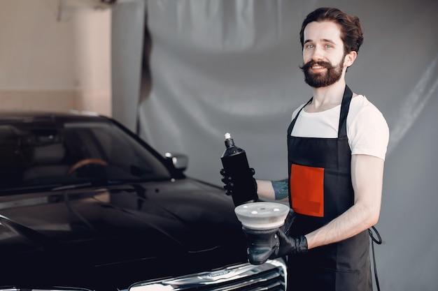 Homem polir um carro em uma garagem Foto gratuita