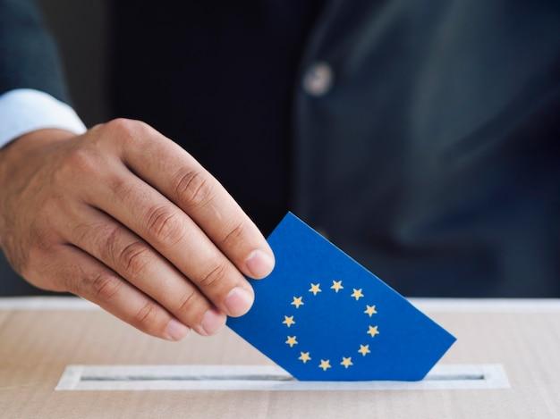 Homem, pôr, um, europeu, eleição, cédula, em, um, caixa Foto gratuita