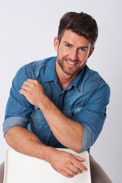 Homem posando com camisa jeans sentado em uma cadeira Foto gratuita