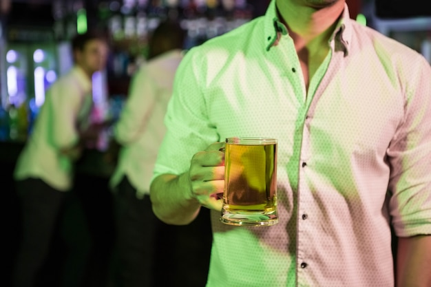 Homem posando com copo de cerveja e amigos na ba Foto Premium