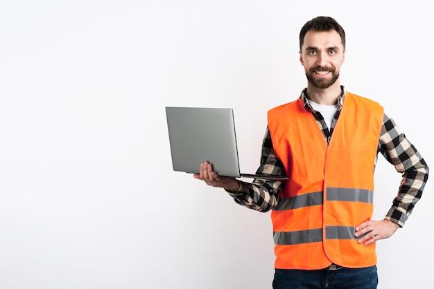 Homem posando com laptop e colete de segurança Foto gratuita