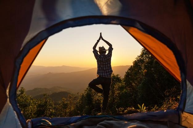Homem, posição, postura ioga, frente, de, acampamento, barraca, fulgor, cima, com, amanhecer, em, manhã Foto gratuita