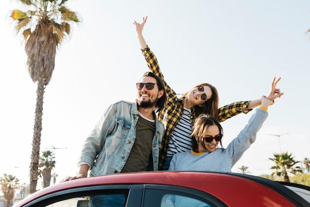 Homem positivo e sorrindo mulheres se divertindo e inclinando-se de auto Foto gratuita
