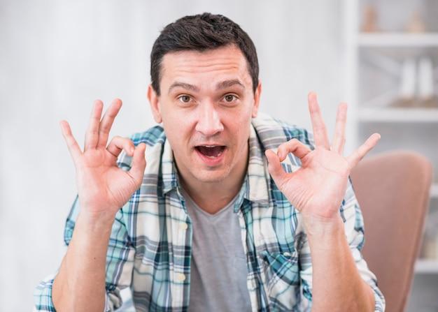 Homem positivo mostrando o gesto bem na cadeira em casa Foto gratuita