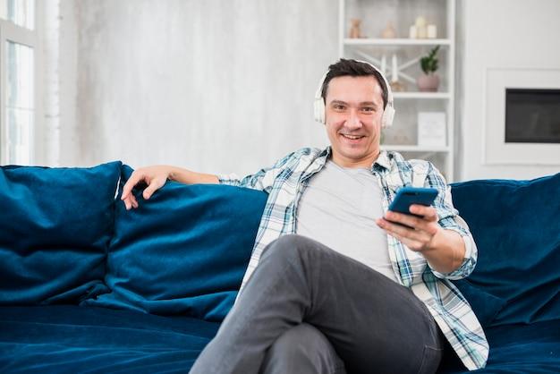 Homem positivo ouvindo música em fones de ouvido e segurando o smartphone no sofá na sala Foto gratuita