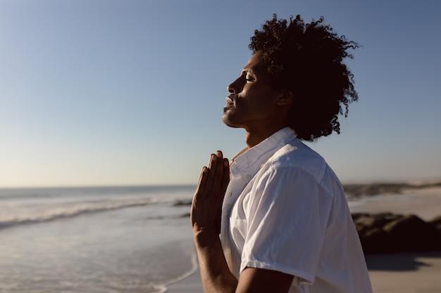 Homem, prática, ioga, praia Foto gratuita