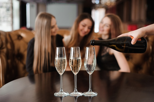 Homem, preenche, copos champanha, para, três, bonito, mulheres jovens, em, restaurante Foto Premium