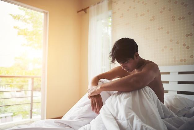 Homem preocupado sentado na cama de manhã, sério, pensando em algo Foto gratuita