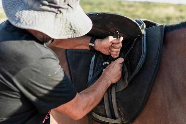 Homem preparando cavalo para passeio Foto gratuita
