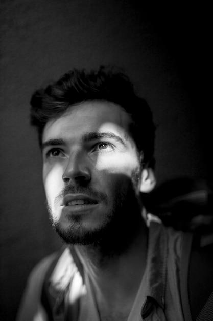 Homem preto e branco na sombra com brilho de luz Foto gratuita