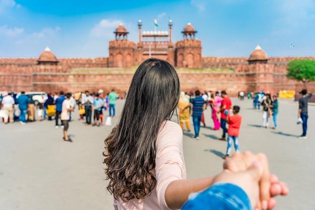 Homem principal do turista asiático da jovem mulher no forte vermelho (lal qila) deli com a bandeira indiana em deli velha, índia. Foto Premium