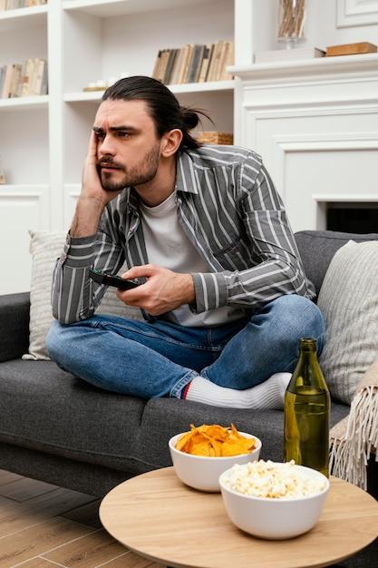 Homem procurando um canal na televisão Foto gratuita