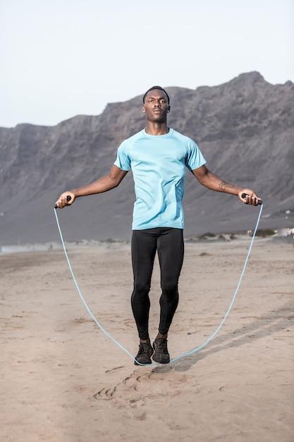 Homem pulando com corda na praia Foto Premium