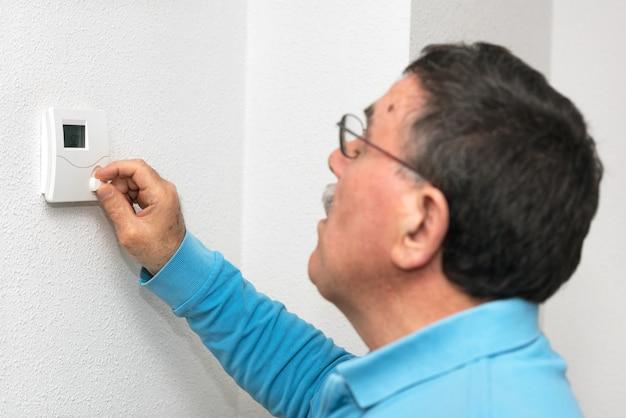 Homem que ajusta o termostato em casa, foco no termostato. escala de temperatura celsius. Foto Premium