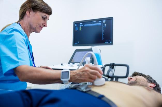 Homem que começ o ultra-som de um abdômen de médico Foto gratuita