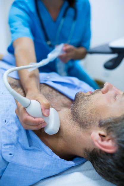 Homem que começ o ultra-som de um tiróide de médico Foto gratuita
