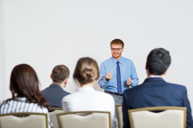 Homem que dá uma palestra para uma audiência Foto gratuita