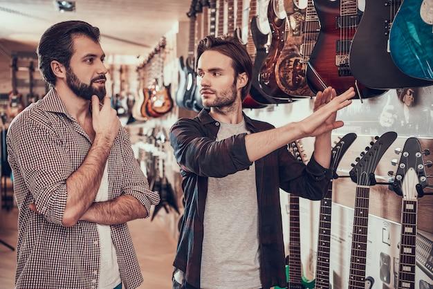 Homem que escolhe a guitarra elétrica na loja do instrumento musical. Foto Premium