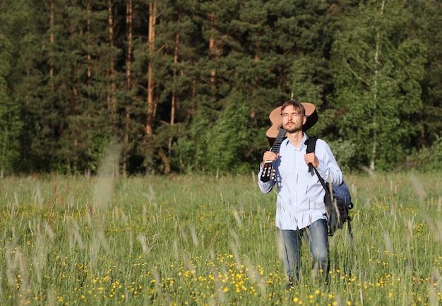 Homem que está a madeira de pinho próxima com guitarra acústica e trouxa. conceito de viagens de verão Foto Premium